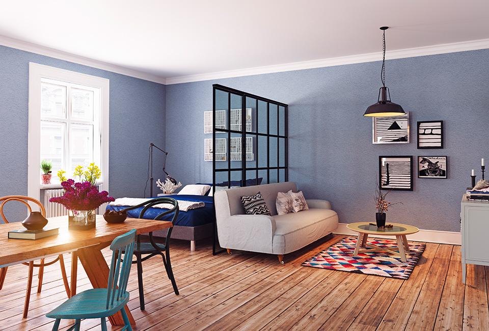 """Parquet e tappeti per creare delle """"isole"""": arredamento interni, open-space con sala da pranzo, camera da letto e salotto con pavimento in parquet e un tappeto colorato"""